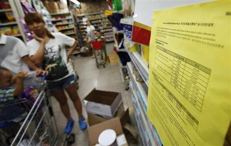 A woman looks at a notice about the product recall of some of Dumex and Abbott's milk powder products at a supermarket in Beijing August 7, 2013. REUTERS/Kim Kyung-Hoon