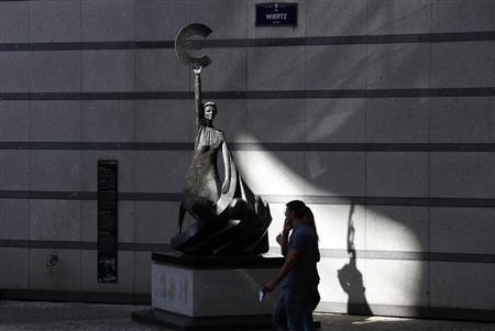 Pedestrians walk past a statue depicting European unity outside the European Parliament in Brussels September 5, 2013. REUTERS/Francois Lenoir