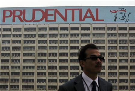 A man stands in front of an advertisement of Prudential displayed on top of a commercial building in Hong Kong March 1, 2010. REUTERS/Bobby Yip