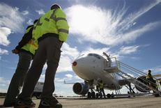 Bombardier employees look at the CSeries aircraft, after its first test flight in Mirabel, Quebec, September 16, 2013. Bombardier Inc's CSeries jetliner successfully completed its first flight on Monday, a key step in a $3.9 billion program to develop the first all-new narrow-body plane of its size in decades. REUTERS/Christinne Muschi