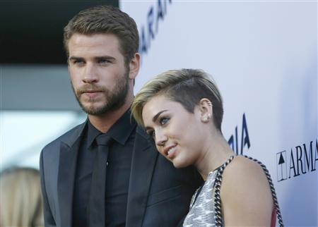 Cast member Liam Hemsworth poses with his fiancee, singer Miley Cyrus, at the premiere of ''Paranoia'' in Los Angeles, California in this file photo taken August 8, 2013. REUTERS/Mario Anzuoni/Files