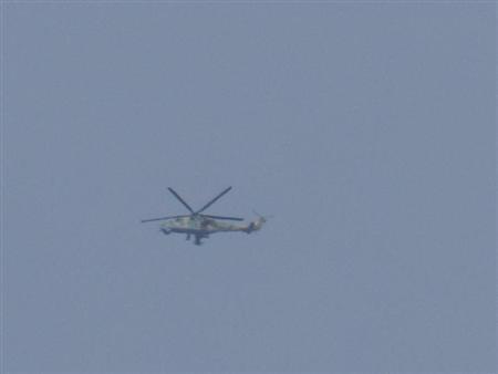 A helicopter belonging to Syrian President Bashar-Al Assad's forces flies over Houla, near Homs, December 3, 2012. REUTERS/Misra Al-Misri/Shaam News Network/Handout