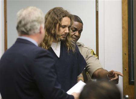 Tim Lambesis (C), lead singer for the heavy metal band As I Lay Dying, enters the courtroom for his arraignment in San Diego North County court in Vista, California in this May 9, 2013 file photo. REUTERS/Lenny Ignelzi/Pool