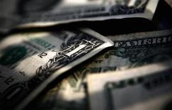 Долларовые купюры в Торонто 26 марта 2008 года. Американский доллар достиг во вторник минимума четырех недель в ожидании итогов двухдневного совещания ФРС США, на котором может быть принято решение о небольшом сокращении программы выкупа облигаций. REUTERS/Mark Blinch