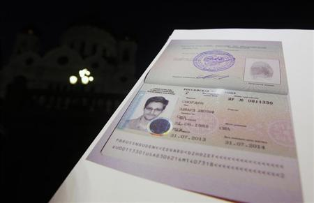 Fugitive former U.S. spy agency contractor Edward Snowden's new refugee documents granted by Russia is seen during a news conference in Moscow August 1, 2013. REUTERS/Maxim Shemetov