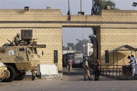 Egyptian army soldiers guard with armoured personnel carriers (APC) in front of the main gate of Torah prison on the outskirts of Cairo, August 22, 2013. REUTERS/Louafi Larbi