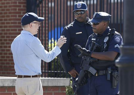 A visitor at the main gate of the Washington Navy Yard is stopped to have his identification checked in Washington, September 17, 2013. REUTERS/Jason Reed