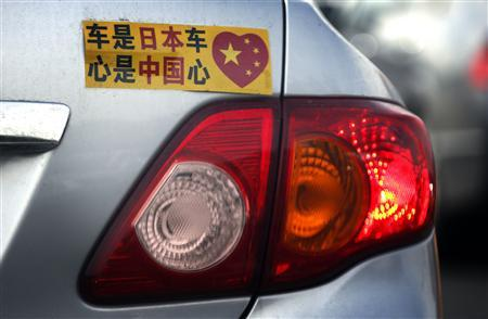 A Toyota car with a sticker attached to the rear can be seen along a main road in central Beijing in this October 16, 2012 file photo. REUTERS/David Gray/Files