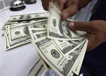 Работник обменного пункта в Маниле считает американские доллары 10 августа 2011 года. Рубль в начале торгов среды торгуется вблизи закрытия предыдущего торгового дня, рынок занял нейтральную позицию в ожидании вечернего решения центробанка США, от которого ждут сокращения программы выкупа облигаций. Интрига кроется в размере этого сокращения. REUTERS/Romeo Ranoco