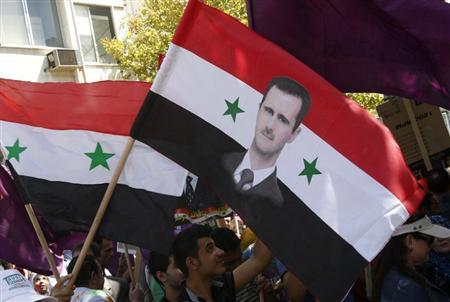 Supporters of Syria's President Bashar al-Assad wave a Syrian national flag depicting Assad's portrait during a rally in front of the parliament building under the slogan ''No aggression on Syria'', in Damascus September 17, 2013. REUTERS/Khaled al-Hariri