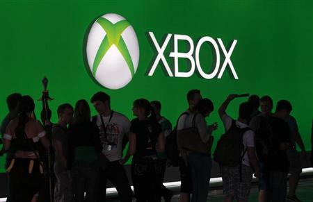 Visitors walk past an advertising placard of the Xbox One at the Microsoft Games exhibition stand during the Gamescom 2013 fair in Cologne August 23, 2013. REUTERS/Ina Fassbender/Files