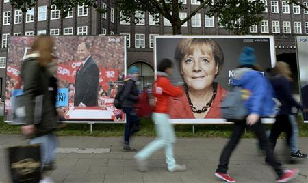 Teenagers pass election posters of Social Democratic top candidate Peer Steinbrueck (SPD) (L) and German Chancellor Angela Merkel (CDU) in Hamburg, September 17, 2013. REUTERS/Fabian Bimmer