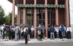 Люди стоят у кофейни Starbucks, закрытую полицией после стрельбы в здании ВМС в Вашингтоне 16 сентября 2013 года. Глава Starbucks Corp Говард Шульц просит клиентов не ходить в кофейни с огнестрельным оружием, что означает сдвиг в политике компании на фоне яростных дискуссий на тему ограничений на владение оружием в США, возникших после серии массовых расстрелов. REUTERS/Joshua Roberts