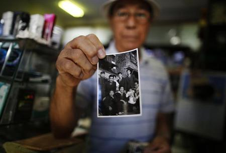 Resident Kohei Jinno, 79, shows a photograph of himself (2nd L wearing suit) taken on January 2, 1957 in front of his previous home, at his shop inside Kasumigaoka apartment complex which is located near the National Olympic Stadium in Tokyo September 18, 2013. REUTERS/Issei Kato