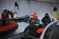 Офицер российской береговой охраны (справа) наводит ствол на активиста Greenpeace, протестующего у борта нефтедобывающей платформы Газпрома в арктическом Печорском море 18 сентября 2013 года. Береговая охрана открыла предупредительный огонь и задержала активистов Greenpeace, вскарабкавшихся на арктическую нефтяную платформу Газпрома ради протеста против потенциальной угрозы экологии вслед за ожидаемым в этом году началом добычи. REUTERS/Denis Sinyakov/Greenpeace/Handout via Reuters