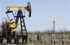 Работник Роснефти у станка-качалки на месторождении Юганскнефтегаза близ Нефтеюганска 26 апреля 2006 года. Минфин РФ видит резерв для роста доходов федерального бюджета в 2014 году в повышении НДПИ на нефть при одновременном снижении экспортной пошлины на сырье, однако ведомство по-прежнему надеется, что пошлина на мазут сравняется с нефтяной уже в 2015 году. REUTERS/Sergei Karpukhin