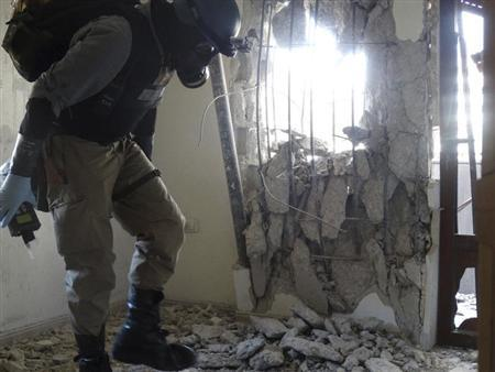 A U.N. chemical weapons expert, wearing a gas mask, inspects one of the sites of an alleged chemical weapons attack in the Damascus' suburb of Zamalka August 29, 2013. REUTERS/Mohammad Abdullah
