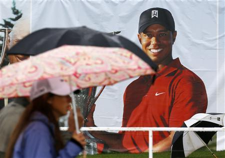 Golf fans walk past a poster of Tiger Woods during a rain delay at the BMW Championship golf tournament at the Conway Farms Golf Club in Lake Forest, Illinois, September 15, 2013. REUTERS/Jim Young
