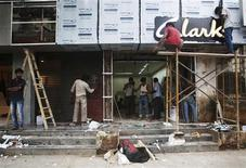Men work at the site of a new shoe store on a street in Mumbai September 11, 2013. REUTERS/Danish Siddiqui