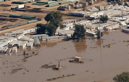 An oil storage tank on a well pad lies toppled near portable buildings surrounded with flood waters in Weld County, Colorado September 17, 2013. REUTERS/Rick Wilking