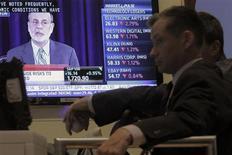 Трейдеры смотрят на выступление главы ФРС Бена Бернанке по телевизору на Нью-Йоркской фондовой бирже 18 сентября 2013 года. Федеральная резервная система США решила сохранить ежемесячный объем скупки активов на уровне $85 миллиардов, удивив финансовые рынки, которые ожидали сокращение программы стимулов на $10 миллиардов. REUTERS/Brendan McDermid