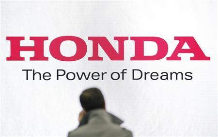 A man stands in front of a logo of Honda Motor at the company showroom in Tokyo January 31, 2013. REUTERS/Issei Kato
