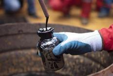 Рабочий компании PDVSA берет образец сырой нефти из нефтяной скважины в Моричале 28 июля 2011 года. Китайская нефтяная компания CNPC поможет государственной нефтяной компании Венесуэлы PDVSA в разработке блока Хунин-10 в нефтяном поясе Ориноко, сообщил министр нефтяной промышленности Венесуэлы Рафаэль Рамирес. REUTERS/Carlos Garcia Rawlins
