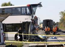 Спасатели изучают место столкновения автобуса и поезда в Оттаве 18 сентября 2013 года. По меньшей мере пятеро погибли в столкновении поезда и двухэтажного автобуса в Оттаве, сообщил представитель пожарной службы города Марк Мессье. REUTERS/Chris Wattie