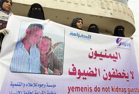 Journalists and human rights activists hold a banner during a protest to demand the release of journalist Judith Spiegel and her partner Boudewijn Berendsen, the Dutch couple who have been kidnapped in Yemen, outside the home of Yemeni President Abd-Rabbu Mansour Hadi in Sanaa August 1, 2013. REUTERS/Mohamed al-Sayaghi