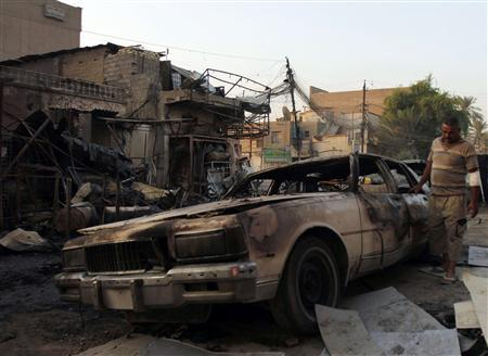 A man looks at a damaged vehicle a day after a bomb attack in Baghdad, in this file picture taken September 16, 2013. REUTERS/Ahmed Saad/Files