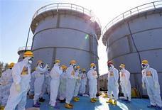 Primeiro-ministro do Japão, Shinzo Abe (de capacete vermelho), visita área com tanques de armazenamento de água radiotiva, na usina nuclear de Fukushima Daiichi, no Japão. Abe ordenou o descarte de dois reatores nucleares da usina de Fukushima que sobreviveram ao tsunami de 2011, uma medida que ameaça complicar o plano de restruturação apresentado a credores pela empresa que opera a planta. 19/09/2013. REUTERS/Pool
