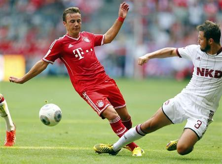 Mario Goetze (L) of FC Bayern Munich is challenged by Per Nilsson of FC Nuremberg during their German first division Bundesliga soccer match in Munich August 24, 2013. REUTERS/Michael Dalder