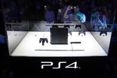 Посетители выставки Tokyo Game Show в Тибе фотографируют новую игровую приставку PlayStation 4 19 сентября 2013 года. Sony Corp намерена реализовать 5 миллионов игровых консолей PlayStation 4 за менее чем 5 месяцев с начала продаж, который совпадет с запуском конкурента Xbox One от Microsoft Corp. REUTERS/Yuya Shino