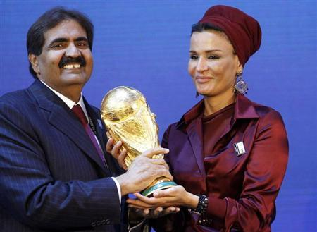 Qatar's Emir Sheikh Hamad bin Khalifa al Thani and his wife Sheikha Moza Bint Nasser al-Misnad hold a copy of the World Cup trophy he received from FIFA President Sepp Blatter (unseen) after the announcement that Qatar will be the host nation for the FIFA World Cup 2022, in Zurich in this December 2, 2010 file photo. REUTERS/Arnd Wiegmann/Files