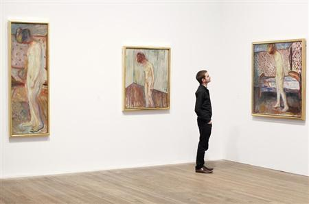 Duncan Holden of the Tate poses with three paintings of Edvard Munch's ''Weeping Woman'' series at the Tate Modern in London's Southbank, June 26, 2012. REUTERS/Andrew Winning