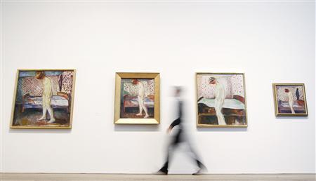 Duncan Holden of the Tate poses with four paintings of Edvard Munch's ''Weeping Woman'' series at the Tate Modern in London's Southbank, June 26, 2012. REUTERS/Andrew Winning