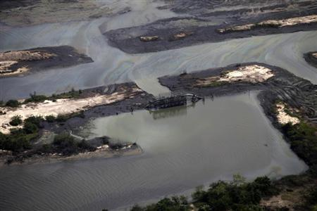 A view is seen of an illegal oil refinery near a flowstation at the Nembe trunk carriage line, during an aerial tour by the Royal Dutch Shell company, near Nigeria's oil hub city of Port Harcourt March 22, 2013. REUTERS/Akintunde Akinleye