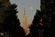The moon rises at sunset behind New York's Empire State building as a woman runs along a promenade in Hoboken, New Jersey, September 17, 2013. REUTERS/Gary Hershorn