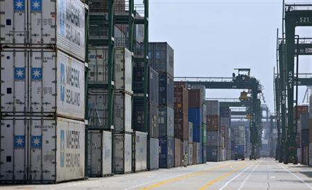 A worker walks past stacks of containers at the PSA International's Pasir Panjang terminal in Singapore December 18, 2008. REUTERS/Tim Chong