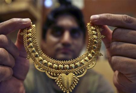 A salesman poses with a gold necklace at a jewellery shop in Jammu July 11, 2008. REUTERS/Amit Gupta/Files