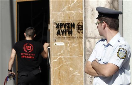 A Greek police officer (R) watches as a member of the Golden Dawn far-right party enters the party's headquarters in Athens September 18, 2013. REUTERS/John Kolesidis