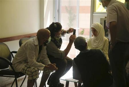 A U.N. chemical weapons expert (2nd L) takes a picture of a person affected by an apparent gas attack, at a hospital where she is being treated , in the Damascus suburb of Zamalka August 29, 2013. REUTERS/Mohamed Abdullah