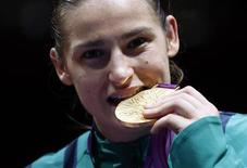 Katie Taylor of Ireland bites her gold medal following the presentation ceremony for the Women's Light (60kg) boxing competition at the London Olympic Games August 9, 2012. REUTERS/Murad Sezer