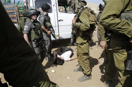 French diplomat Marion Castaing lays on the ground after Israeli soldiers carried her out of her truck containing emergency aid, in the West Bank herding community of Khirbet al-Makhul, in the Jordan Valley September 20, 2013. REUTERS/Abed Omar Qusini