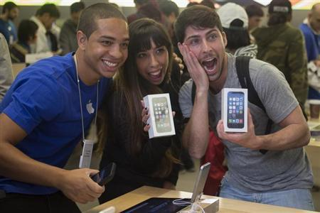 Alejandro de Rosa (R) and Melisa Racineti of Buenos Aires, Argentina pose with their new Apple iPhone 5s phones with Apple employee Jay at the Apple Retail Store on Fifth Avenue in Manhattan, New York September 20, 2013. REUTERS/Adrees Latif