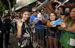 "Cast member Selena Gomez waves while greeting fans at the premiere of ""Getaway"" in Los Angeles, California August 26, 2013. REUTERS/Mario Anzuoni"