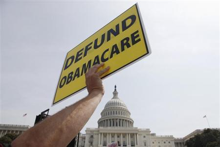 A man holds a sign at the Tea Party Patriots 'Exempt America from Obamacare' rally on the west lawn of the U.S. Capitol in Washington, September 10, 2013. REUTERS/Jonathan Ernst