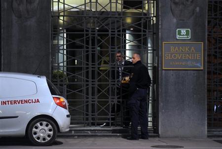 Security personnel speak in front of the National Bank of Slovenia building in Ljubljana, April 15, 2013. REUTERS/Srdjan Zivulovic