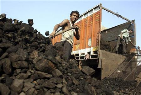 Labourers work inside a coal yard on the outskirts of Ahmedabad November 30, 2010. REUTERS/Amit Dave/Files