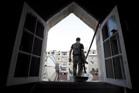 A Free Syrian Army fighter walks through a window in Salah al-Din neighbourhood in central Aleppo, September 20, 2013. REUTERS/Loubna Mrie